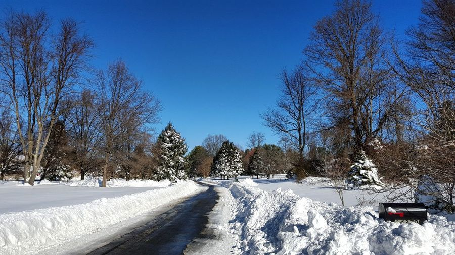 Empty Road On Snow Covered Field Against Clear Blue Sky