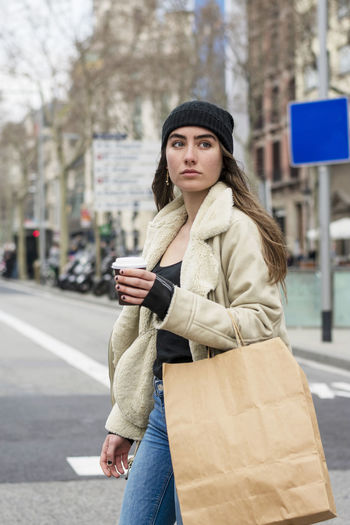 Portrait of young woman standing on mobile phone in city