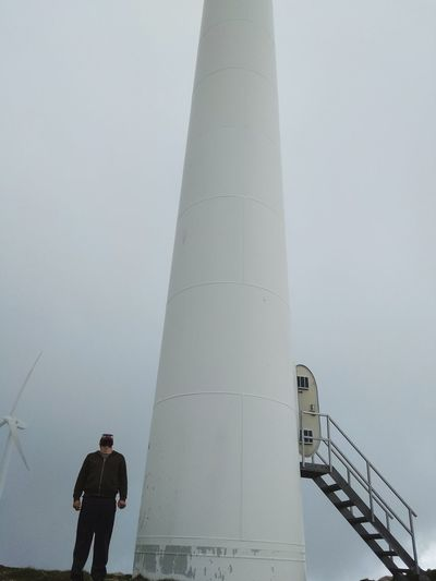Low angle view of man standing by lighthouse against sky