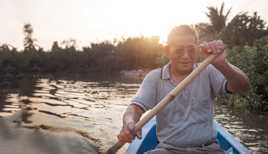 Senior old asian man roll boat in the river in long life active outdoor activity concept person