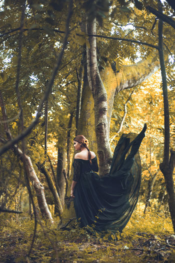 Woman with an elegant dress in the forest