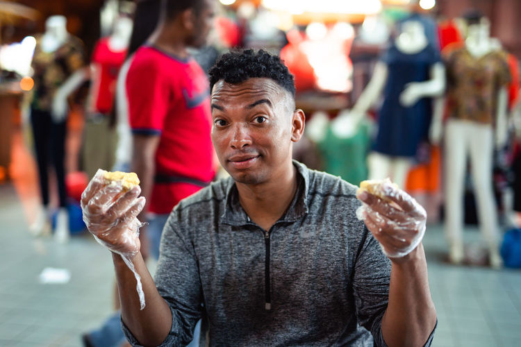 Portrait of man having durian while sitting in store