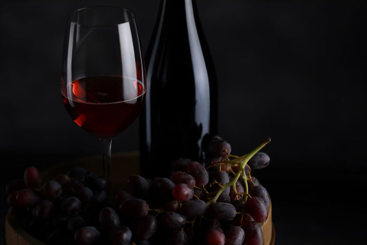 Close-up of red wine glass against black background