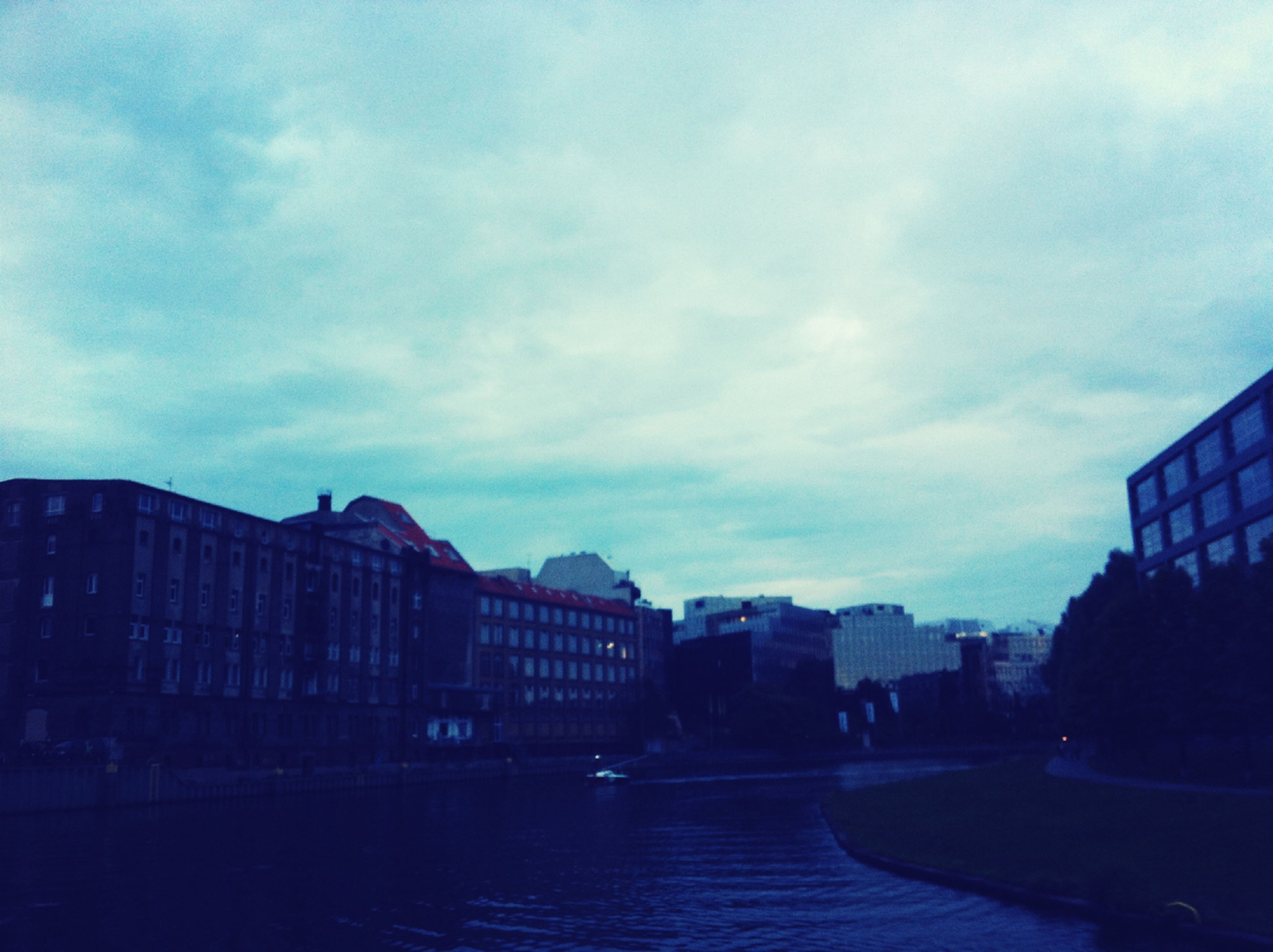 architecture, building exterior, built structure, sky, water, waterfront, cloud - sky, city, river, cloudy, cloud, building, residential building, dusk, residential structure, outdoors, reflection, no people, canal, day