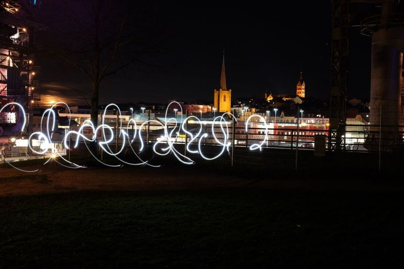 Light Painting Against Illuminated Buildings At Night