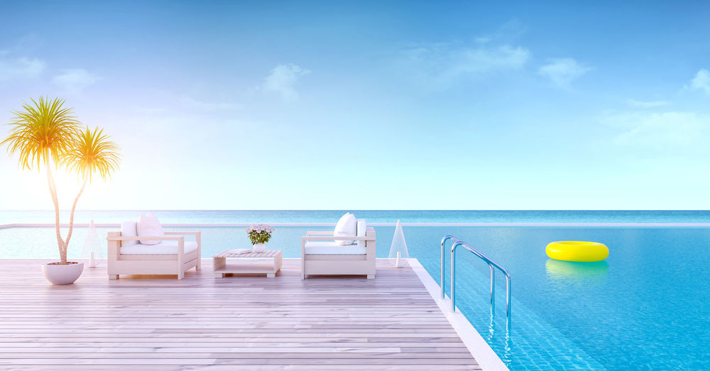 Empty lounge chairs by infinity pool against sky