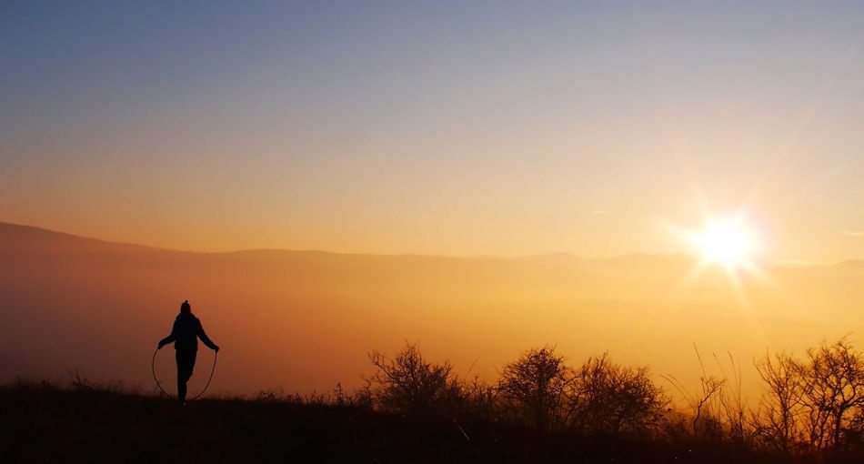 Silhouette Person With Skipping Rope On Field During Sunset