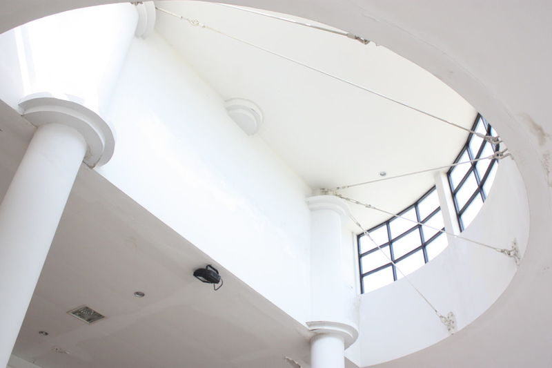Low angle view of spot light on white ceiling