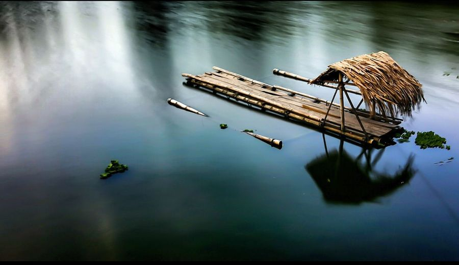 High angle view of thatched roof on wooden raft in river