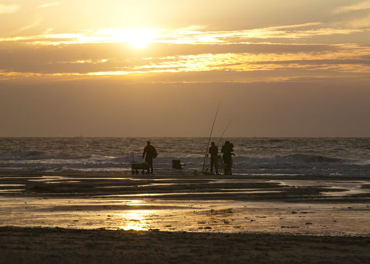 Silhouette people fishing on beach against sky during sunset