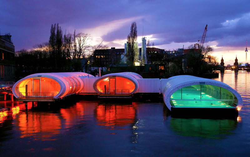 Boats in river against illuminated city at sunset