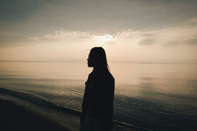 Sunset Sky Water Beauty In Nature One Person Real People Sea Scenics - Nature Silhouette Horizon Over Water Leisure Activity Standing Lifestyles Beach Cloud - Sky Women Horizon Orange Color Nature Outdoors