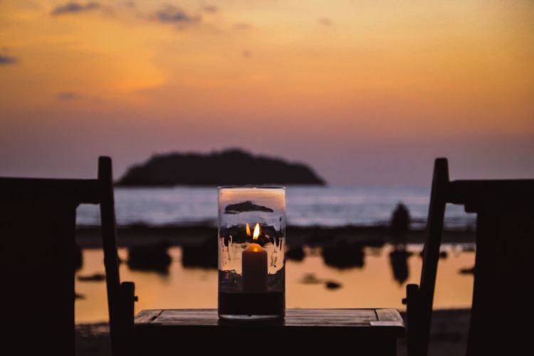 Wine glass on table against sea during sunset
