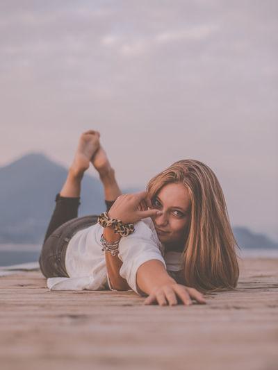 Portrait of woman lying on beach against sky