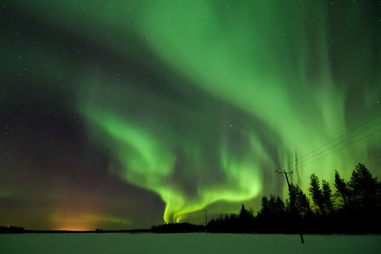 Scenic View Of Aurora Borealis Over Snowy Field At Night