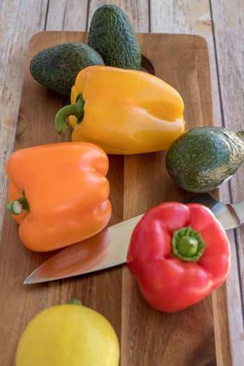 bell peppers and a kitchen knife on a wooden cutting board Yellow Pepper Bell Pepper Bell Peppers Close-up Food Food And Drink Freshness Healthy Eating Indoors  No People Orange Peppers Pepper Raw Food Red Peppers Still Life Vegetable Wellbeing