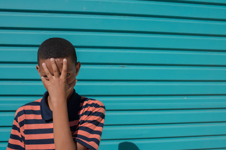 Portrait of boy covering face with hand against shutter