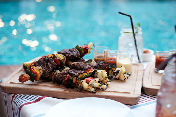 High angle view of barbecued meat and vegetables in skewers on tray at pool party