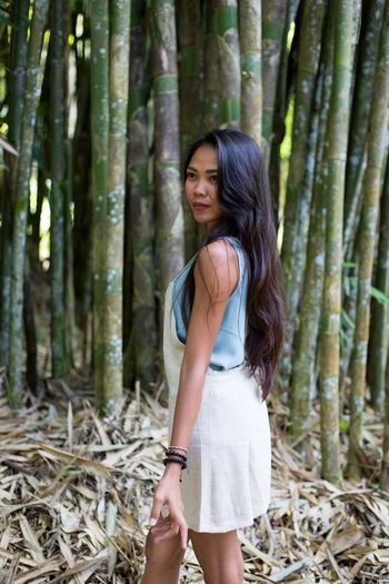 Side View Of Young Woman Looking Away While Standing Against Bamboo Grove