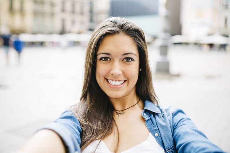 Beautiful young woman taking a selfie with her mobile. Happy Woman Beautiful Woman Beauty City Close-up Day Focus On Foreground Happiness Headshot Looking At Camera One Person Outdoors Outdoors Photograpghy  People Portrait Real People Selfie Smile Smiling Women Young Adult Young Women