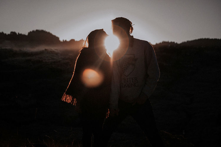 Couple standing on field against sky during sunset