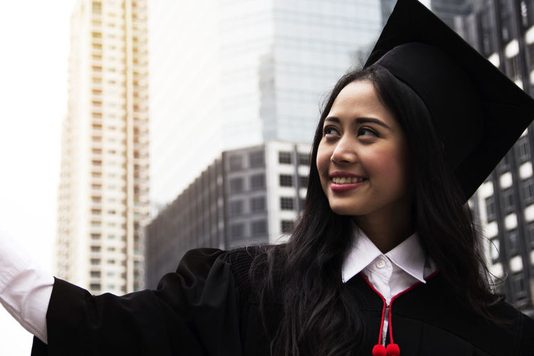 Smiling Young Woman Wearing Graduation Gown In City
