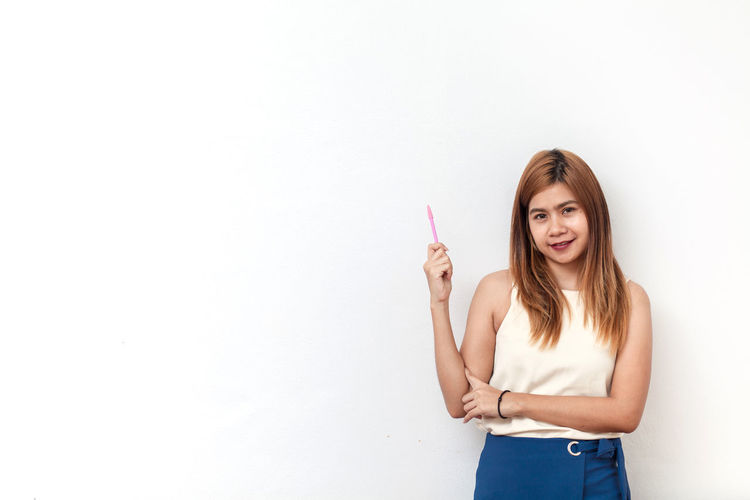 Smiling Businesswoman Standing Against White Background