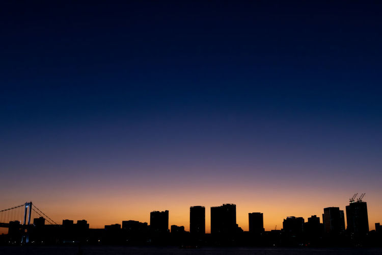 Silhouette buildings against clear sky during sunset