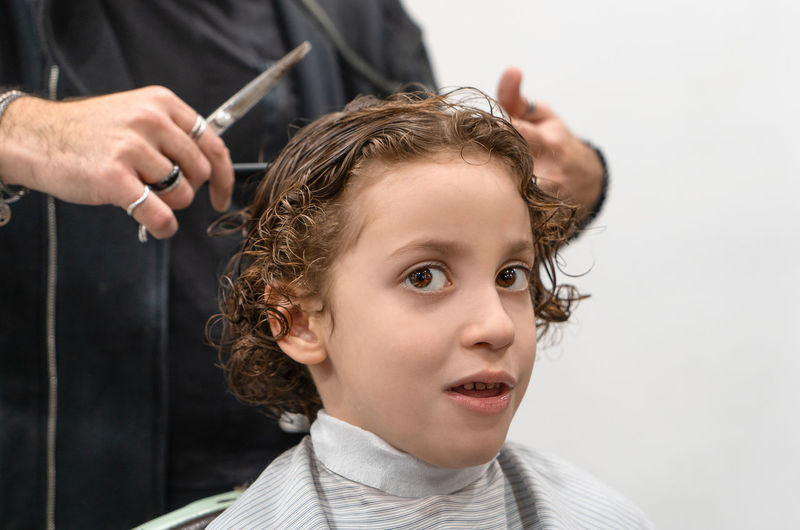 Little kid at barber shop Headshot Childhood Portrait Hair Indoors  Hairstyle Child Hair Care Curly Hair People Males  Human Hair Holding Men Cutting Hair Front View Two People Hairdresser Boys Hand Innocence Scissors Barber Barbershop Shampoo
