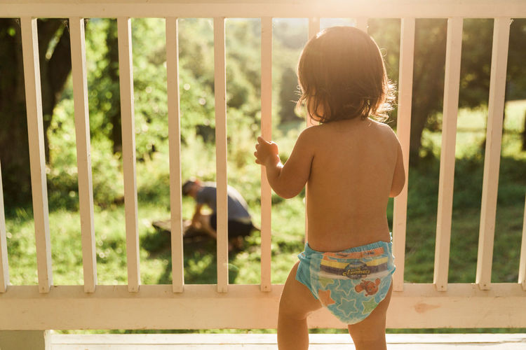 Rear view of shirtless boy standing against blurred background