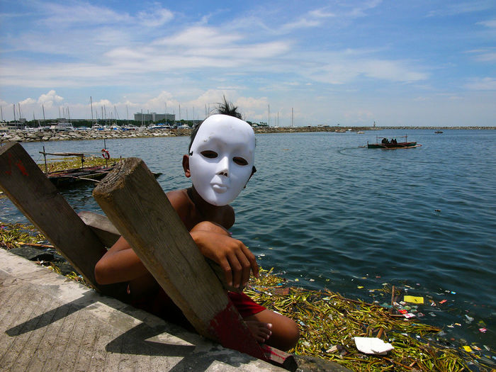 Portrait of shirtless boy wearing mask sitting on ladder by sea