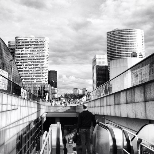 Man On Escalator Leading Towards Railroad Station In City Against Cloudy Sky