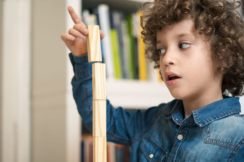 kid playing with wood blocks indoor Kid Playing Game Wood Blocks Jenka One Person Child Curly Hair Indoors  Casual Clothing Headshot Education Hairstyle Concentration Real People Lifestyles Learning Looking Holding Childhood Standing Studying Portrait Balance