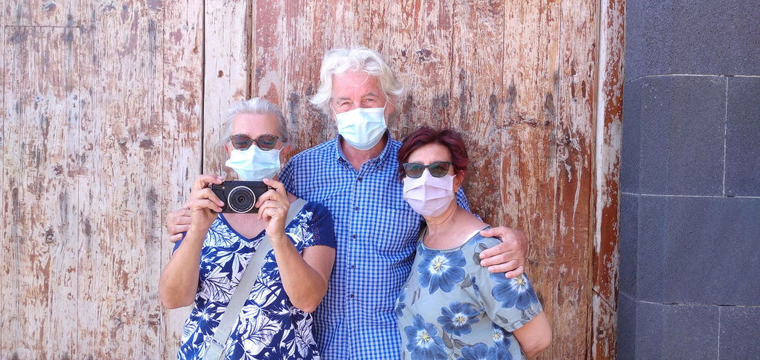 Portrait of friends wearing masks standing against wall