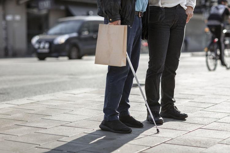 Low section of people walking on sidewalk