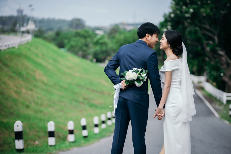 Married couple standing on road in park