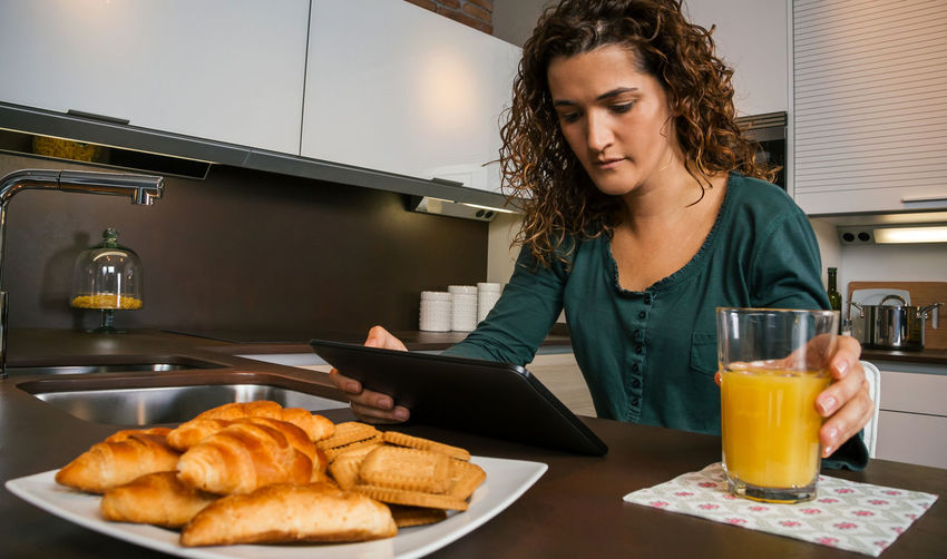 Young woman having breakfast in the kitchen and looking at the tablet Horizontal Croissant Female Girl Orange Juice  Technology Comfortable Enjoying Relax Sitting One News Modern Serious Closeup Biscuits Indoor Internet Real Curly Hair Young Journal Sunday People Digital Holding Reading Web Napkin Shopping Looking Lifestyle Drink Caucasian Home Kitchen Single Tranquility Morning Interested Concentrated Tablet Using Breakfast Pajama Woman Unmarried