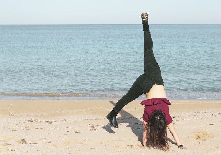 Woman doing cartwheel dance on shore at beach against sky