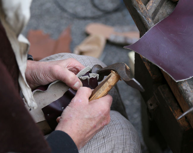 Close-Up Of Cobbler Working While Holding Hammer