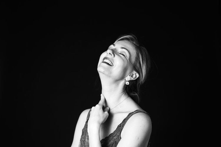 Smiling woman against black background