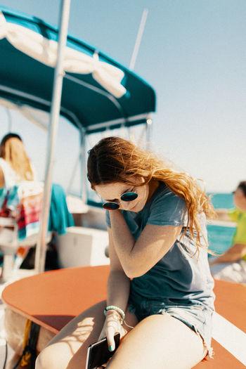Woman wearing sunglasses sitting outdoors
