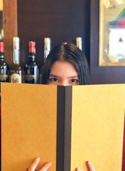 Portrait of young woman with menu in bar