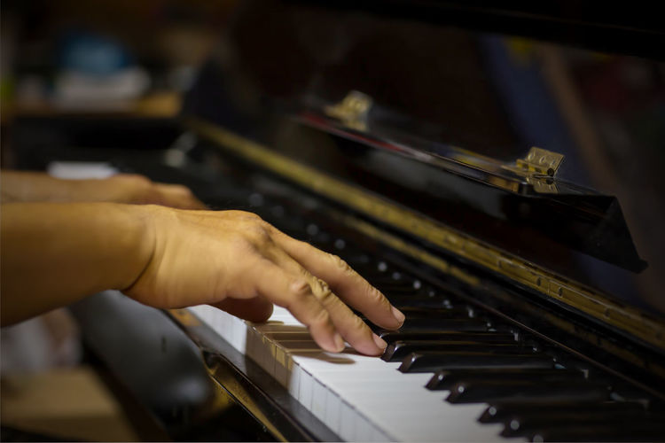 Cropped hands of man playing grand piano