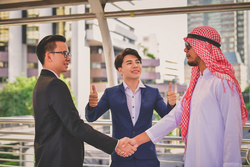 Businessman shaking hands while colleague gesturing on elevated road