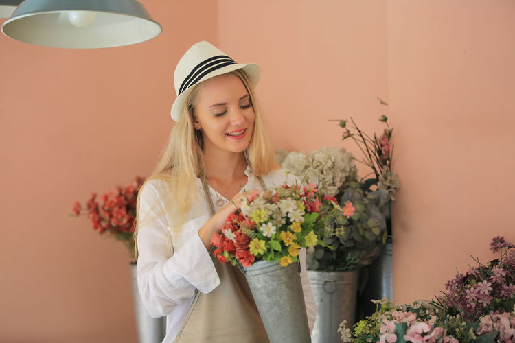Young woman holding flower bouquet against wall