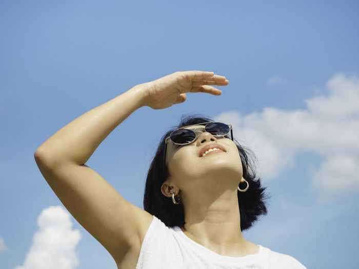 Low angle view of woman wearing sunglasses against sky