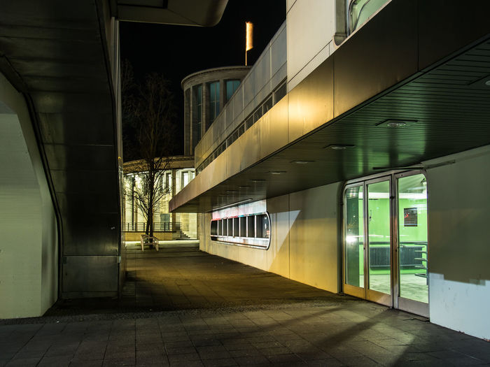 Empty footpath amidst buildings in city at night