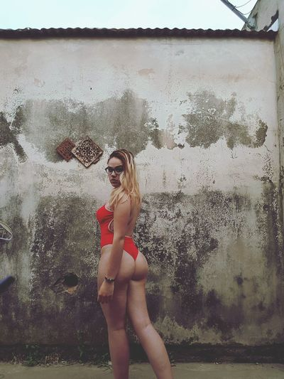 Portrait of seductive woman wearing red one piece swimsuit standing against wall