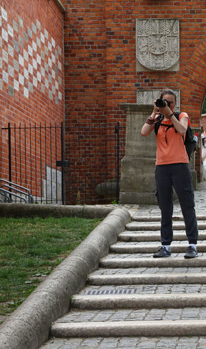 Photographer photographing through camera while standing on steps against building