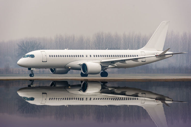 Reflection of airplane in water on airport
